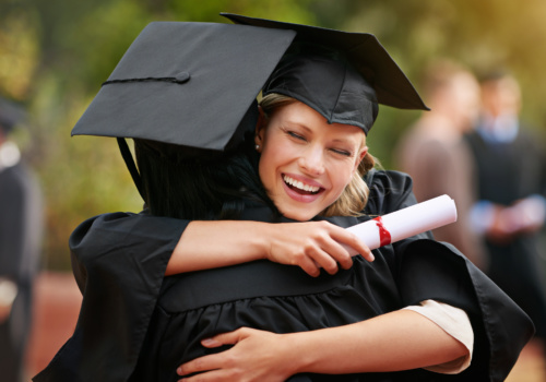 Two students hugging at graduation ceremony