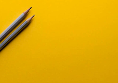 Two grey pencils on yellow background